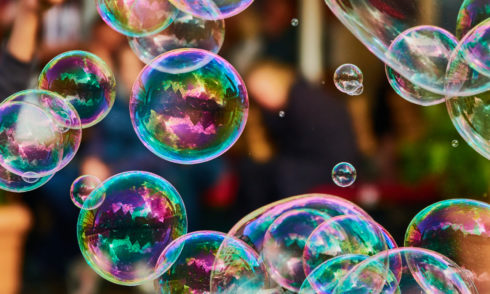 Metallic glowing colorful soap bubbles in the air in front of a blurry abstract background
