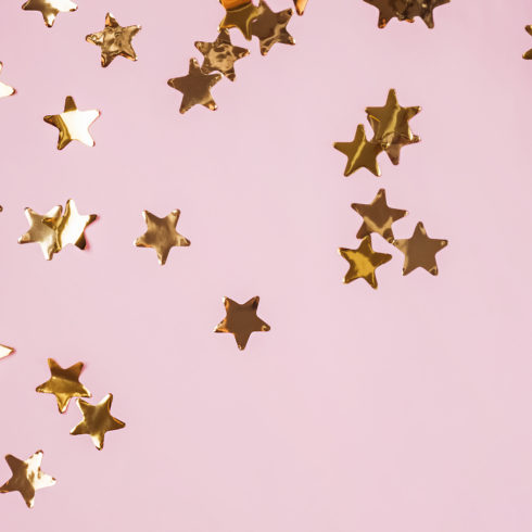 Golden shiny decorative stars on the pink background, top view. Celebration concept