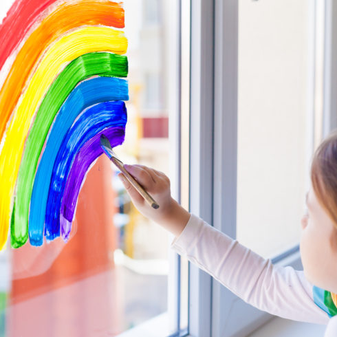 Kids at home. A child girl paints a rainbow on a window during the quarantine for the coronavirus pandemic. Social flash mob in support of society. Let's all be well. Stay at home