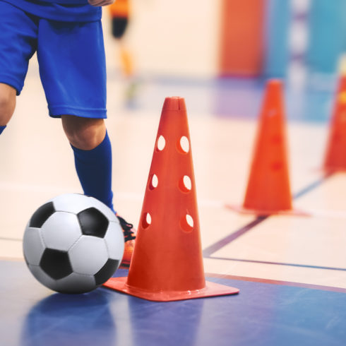 Football futsal training for children. Soccer training dribbling cone drill. Indoor soccer young player with a soccer ball in a sports hall. Player in blue uniform. Sport background